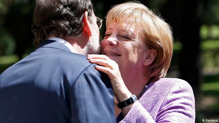 German Chancellor Angela Merkel gestures next to Spain's Prime Minister Mariano Rajoy as they pose before their meeting at Moncloa Palace in Madrid