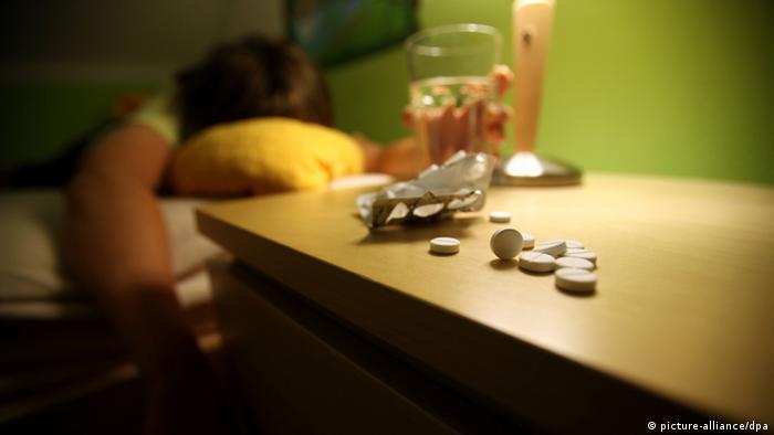 Стакан с водой и таблетки