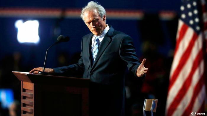 Clint Eastwood se tient devant un podium avec le drapeau américain en arrière-plan.