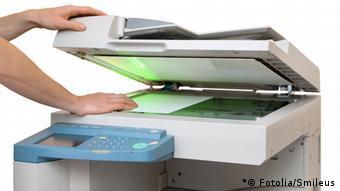 Мужчина закладывает лист бумаги в копировальный аппарат в офисе