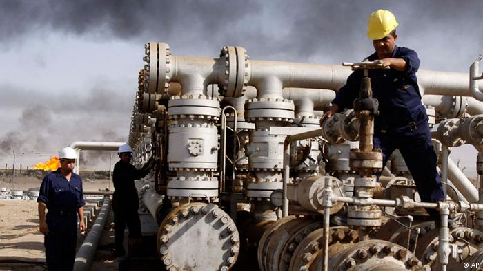 Iraqi workers are seen at the Rumaila oil refinery