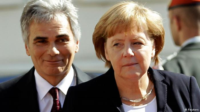 Austrian Chancellor Werner Faymann and German Chancellor Angela Merkel walk to review the guard of honour prior to a meeting in Vienna September 7, 2012. REUTERS/Leonhard Foeger (AUSTRIA - Tags: POLITICS)