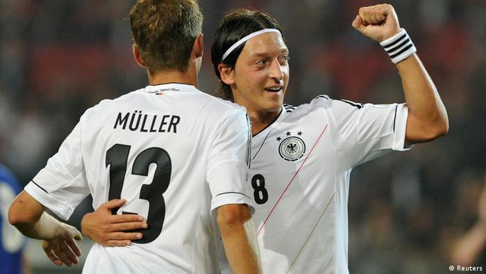 Germany's Mesut Oezil and team mate Thomas Mueller celebrate after scoring during the 2014 World Cup qualification soccer match against Faroe Islands in Hanover September 7, 2012.