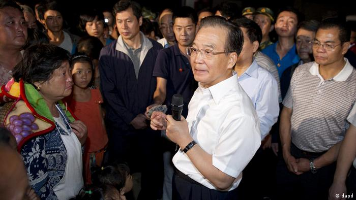 In this photo released by China's Xinhua News Agency, Chinese Premier Wen Jiabao, center, talks to earthquake victims in Yiliang County of Zhaotong, southwest China's Yunnan Province, early Saturday, Sept. 8, 2012. At least 80 people were killed and more than 100,000 residents were evacuated after Friday's quakes toppled thousands of houses and sent boulders cascading across roads in a remote mountainous area along the borders of Guizhou and Yunnan provinces. (AP Photo/Xinhua, Huang Jingwen) NO SALES