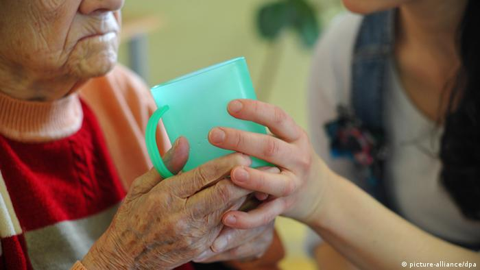 A caregiver braces an elderly woman's hands as she holds a cup Photo: Patrick Pleul