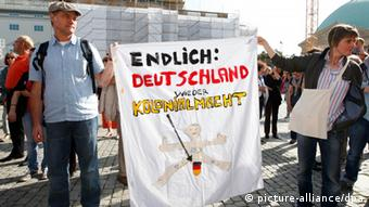 demonstrators with poster: Finally, Germany a colonial power again. Foto: Florian Schuh dpa/lbn