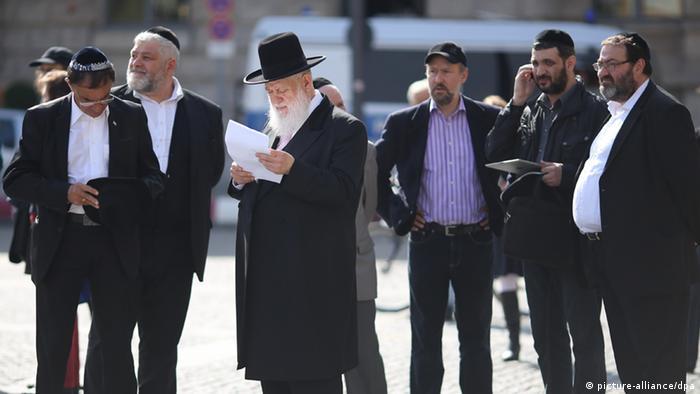 Der orthodoxe Rabbiner Yitzhak Ehrenberg (M) steht auf dem Bebelplatz in Berlin. (Foto: dpa)