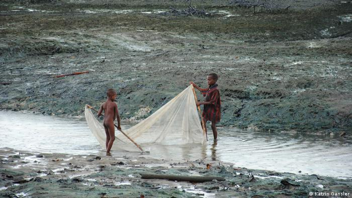 Two boys holding a fishing net into the water