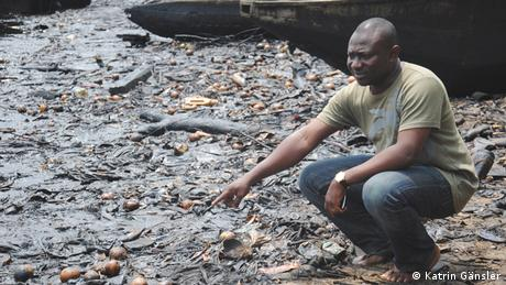 Kentebe Ebriaridor kneels next to a field of dead fish