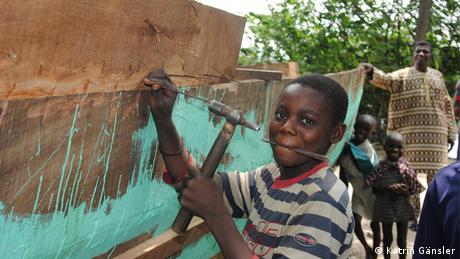 A grinning boy is painting a wooden fishing boat green