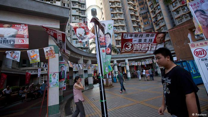 People walk past campaign banners of various candidates for the Legislative Council election campaign in Hong Kong September 9, 2012. Hong Kong residents voted for a new legislature on Sunday, a day after the territory's Beijing-backed leader backed down on a plan to introduce a compulsory Chinese school curriculum after tens of thousands of people took to the streets. REUTERS/Tyrone Siu (CHINA - Tags: POLITICS ELECTIONS)