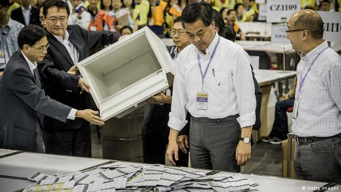 Hong Kong Chief Executive Leung Chun-ying (C) opens a ballot box at a ballot counting centre in Hong Kong on early September 10, 2012. Hong Kong voters went to the polls on September 9 in legislative elections seen as a crucial test for the Beijing-backed government, as calls for full democracy grow and disenchantment with Chinese rule surges. AFP PHOTO / Philippe Lopez (Photo credit should read PHILIPPE LOPEZ/AFP/GettyImages)