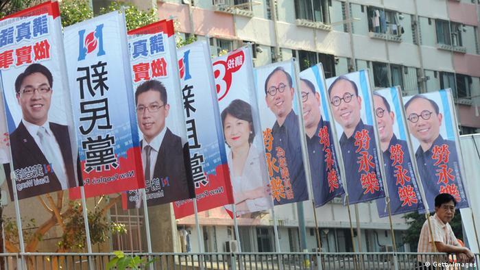 A man stands next to banners promoting candidates running the legislative elections, outside a public housing estate in Hong Kong