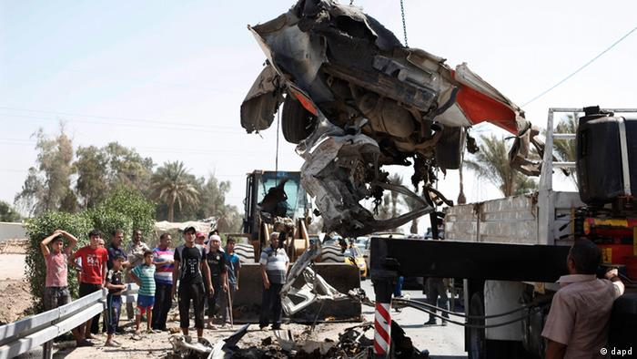 A destroyed car is moved from the scene of a car bomb attack in the town of Taji, about 12 miles (20 kilometers) north of Baghdad, Iraq, Sunday, Sept. 9, 2012. In violence, which struck at least 10 cities across the nation Insurgents killed at least 39 people in a wave of attacks against Iraqi security forces on Sunday, gunning down soldiers at an army post and bombing police recruits waiting in line to apply for jobs, officials said. (Foto:Karim Kadim/AP/dapd)