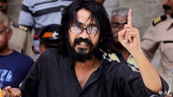Indian political cartoonist Aseem Trivedi gestures after he is arrested by the police on charges of mocking the Indian constitution in his drawings, in Mumbai, India, Sunday, Sept. 9, 2012 (Photo: AP)