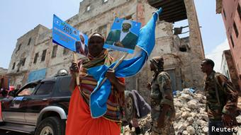 A woman holds up election campaign posters of Somalia's President Sheikh Sharif Ahmed in Mogadishu, September 9, 2012. The presidential election will be held on September 10. REUTERS/Feisal Omar (SOMALIA - Tags: ELECTIONS POLITICS TPX IMAGES OF THE DAY)