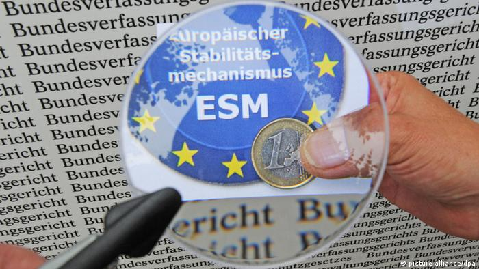 a magnifying glass in front of the letters ESM and a euro coin Photo: Uli Deck dpa/lsw