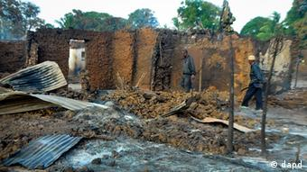 Two men observe remains of a burnt mud built house (Photo by AP/dapd)