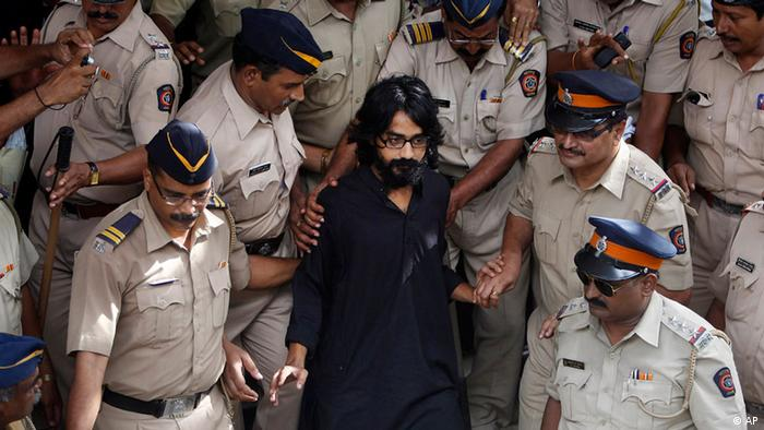 Indian policemen escort political cartoonist Aseem Trivedi, center in black as they leave a court in Mumbai, India, Monday, Sept. 10, 2012. Trivedi whose drawings mock Indian government corruption has been jailed on a sedition charge in an arrest that was widely condemned Monday as evidence of political leaders' increasing intolerance of criticism. (Foto:Rafiq Maqbool/AP/dapd)