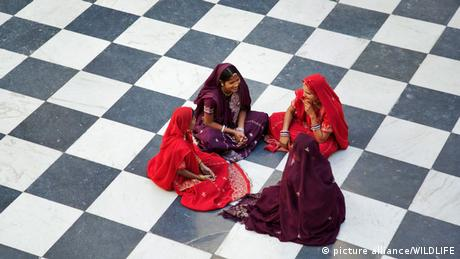 Indian women in traditional saris sitting on the chequered floor of the Peacock courtyard at the City Palace Complex in Udaipur.