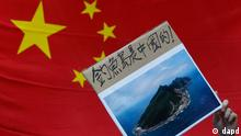 A protester demonstrating against Japan's claim to disputed islands holds a picture of the rocky islands, known as Senkaku to Japanese and Diaoyu to Chinese, reading