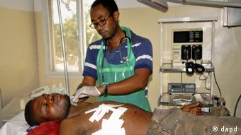A doctor attends to a patient who suffered a gunshot wound to the chest (Photo:AP/dapd)