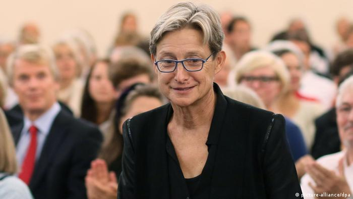 Judith Butler stands amidst a crowd of people.
