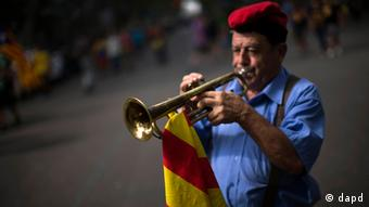Ferran Estrada Porta, 79, wearing the traditional cup or barretina and holding a Catalan flag, plays his trumpet on the street in Barcelona, Spain, Tuesday, Sept. 11, 2012 (AP)