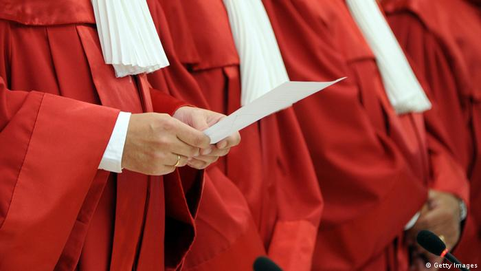 The red-and-white robes of three judges (Photo: Uli Deck/dpa)
