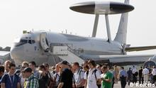 Visitors queue up in front of a NATO Airborne Warning and Control Systems aircraft (AWACS) to have a look inside a Boeing 747-8 aircraft (not pictured) during the opening day of ILA Berlin Air Show in Selchow near Schoenefeld south of Berlin, September 11, 2012. REUTERS/Tobias Schwarz (GERMANY - Tags: TRANSPORT TRAVEL ENTERTAINMENT MILITARY)