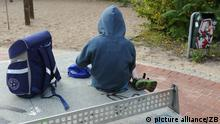 Kind mit Schulranzen auf Spielplatz