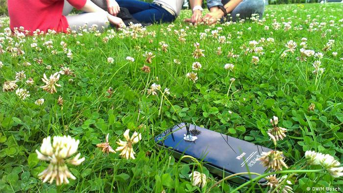 A smartphone lies unattended on grass - a symbol for cyber insecurity