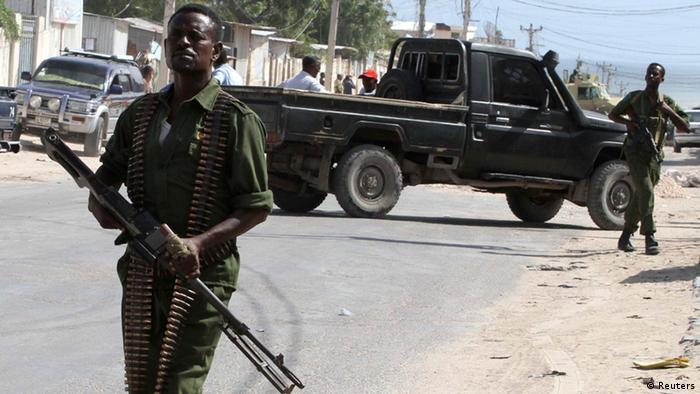 Somali government soldiers patrol the scene of an explosion in the capital of Mogadishu.