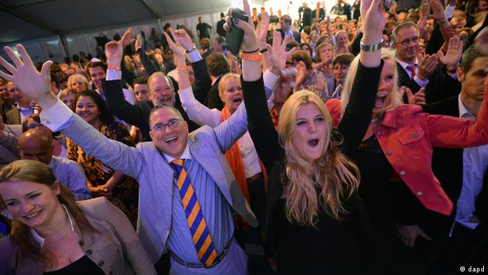 Supporters of Dutch prime minister and Liberal Party leader Mark Rutte celebrate after exit poll results for the parliamentary elections were announced in The Hague, Netherlands, Wednesday Sept. 12, 2012. An exit poll commissioned by the two biggest Dutch news broadcasters has predicted a narrow election victory for the Prime Minister Mark Rutte's free-market VVD party. The exit poll, which will be updated with late votes, gave the VVD 41 of the House of Representatives' 150 seats and the center-left Labor Party 40 votes. The poll has a 1.5 percent margin of error, and the broadcasters said the final result was still too close to call. (AP Photo/Ermindo Armino)