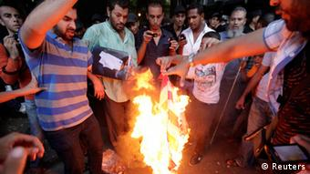 Egyptian protesters burn the US flag during a demonstration outside the US embassy in Cairo, as demonstrators gathered to condemn what they said was a film being produced in the United States that insulted Prophet Mohammad