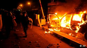 A riot policeman passes burning vehicles during clashes outside the U.S. embassy in Cairo(Foto:Hussein Tallal/AP/dapd)