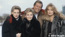 Irish actress Alison Doody, British actress Fiona Fullerton, British actor Roger Moore and US actress Tanya Roberts pose for a group portrait at Pinewood Studios in London, in Iver Heath, England, United Kingdom, 1985. The four actors were at the studios to shoot the new James Bond film, 'A View To A Kill'. (Photo by Fox Photos/Hulton Archive/Getty Images)