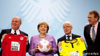 Uli Hoeneß (l-r), Angela Merkel (CDU), Reinhard Rauball Wolfgang Fürstner displaying the special jersey and footballs at the Chancellry in Berlin (dpa)