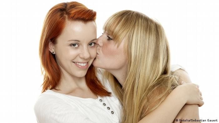 One young woman kissing her friend's check (Fotolia/Sebastian Gauert)