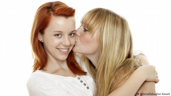 Eine blonde Frau küsst eine rothaarige Frau, die in die Kamera strahlt, auf die Wange (Foto: Fotolia/Sebastian Gauert).