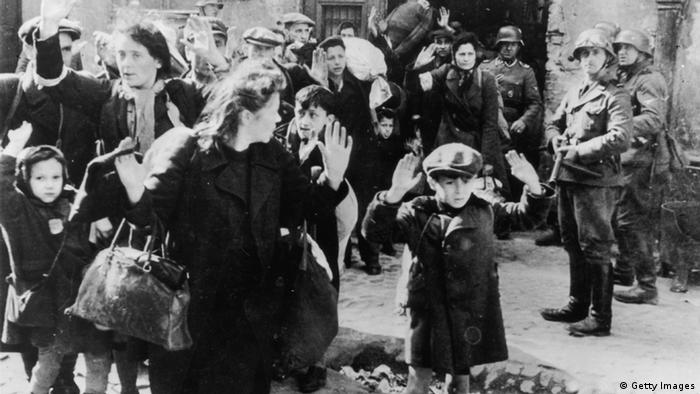 WARSAW, POLAND: A Nazi SS-man inspects a group of Jewish workers in April 1943 in the Ghetto of Warsaw. In November 1940, the Germans established the Warsaw ghetto. The Jewish population still living outside was brought inside the special area, and the Polish living within the designated ghetto boundaries were ordered to move out. On November 15th no Jew was allowed to leave the Jewish precincts. In the Summer of 1942, about 300,000 Jews were deported to Treblinka. When reports of mass murder in the killing center leaked back to the ghetto, a surviving group of mostly young people formed an organisation called Z.O.B. (Zydowska Organizacja Bojowa, Jewish Fighting Organisation) calling for the Jewish people to resist. On April 19, 1943 the Warsaw ghetto uprising began after German troops and police entered the ghetto to deport its surviving inhabitants. Seven hundred and fifty fighters fought for nearly a month. But on May 16, 1943, the revolt ended The Germans had slowly crushed the resistance. Of the more than 56,000 Jews captured, about 7,000 were shot, and the remainder were deported to killing centers or concentration camps. (FILM) AFP PHOTO (Photo credit should read AFP/Getty Images)