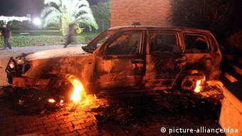 epa03395552 A photo made available on 12 September 2012, shows a vehicle set on fire at the US consulate, in Benghazi, Libya, 11 September 2012. Media reports state that the US ambassador to Libya, Chris Stevens, and three others were killed on 11 September when armed men stormed the US consulate in Benghazi during a protest over a film they said offended Islam. EPA/MUSTAFA EL-SHRIDI