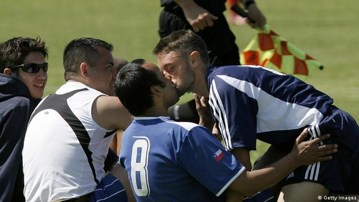 A Chilean footballer (8) is kissed by a US' San Francisco Spikes player during the Gay Football World Championship in Buenos Aires 25 September 2007. The IGLFA World Championship 2007 runs until 29 September. AFP PHOTO / Juan MABROMATA (Photo credit should read JUAN MABROMATA/AFP/Getty Images)