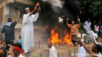A Sudanese demonstrator burns a small German flag as others shout slogans after torching the German embassy in Khartoum during a protest against a low-budget film mocking Islam on September 14, 2012. Around 5,000 protesters in the Sudanese capital angry over the amateur anti-Islam film stormed the embassies of Britain and Germany, which was torched and badly damaged. (Photo: ASHRAF SHAZLY/AFP/GettyImages)