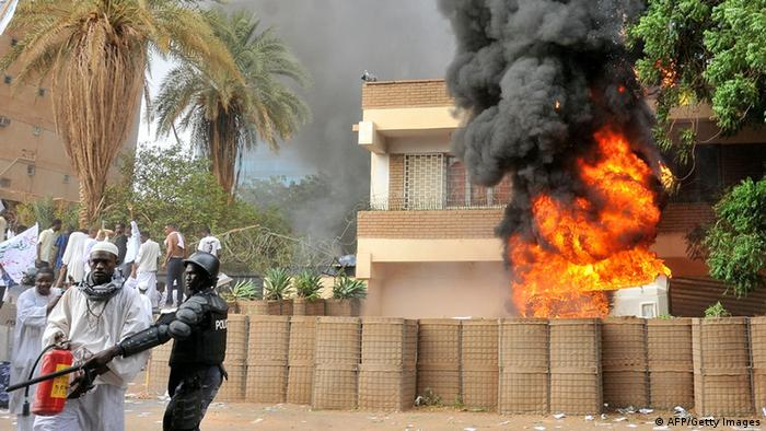 Smoke billows from the burning German embassy in Khartoum as a policeman stands next to a man preparing to extinguish the fire that was caused by protesters demonstrating against a low-budget film mocking Islam on September 14, 2012. Around 5,000 protesters in the Sudanese capital angry over the amateur anti-Islam film stormed the embassies of Britain and Germany, which was torched and badly damaged. AFP PHOTO / ASHRAF SHAZLY (Photo credit should read ASHRAF SHAZLY/AFP/GettyImages)