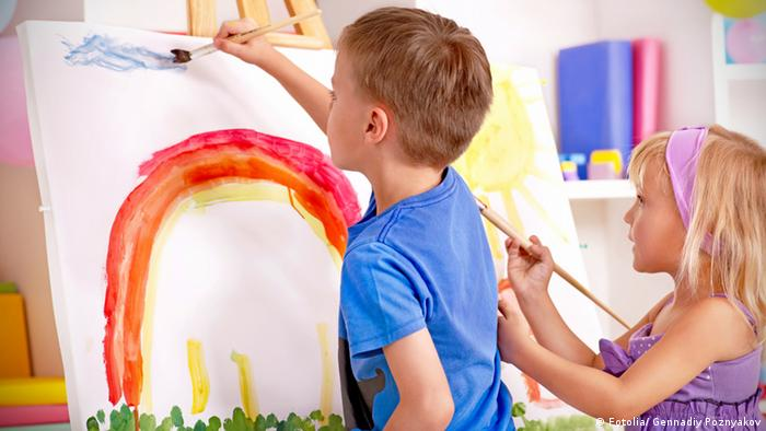 Two small children paint a rainbow image with watercolors (Photo:Fotolia 43469769)