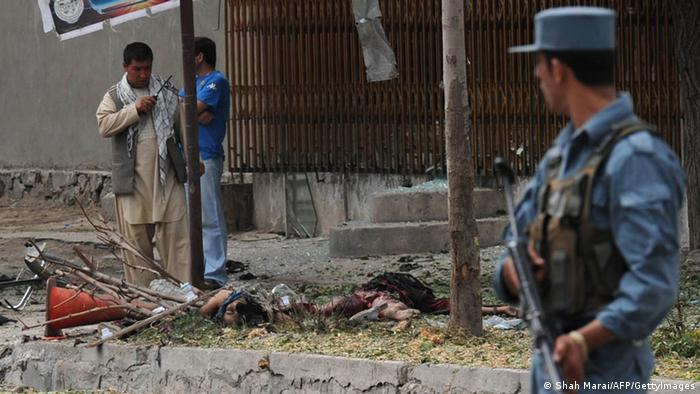 Afghan policemen keep watch near the remains of a suicide attack victim . Photo: SHAH MARAI/AFP/GettyImages