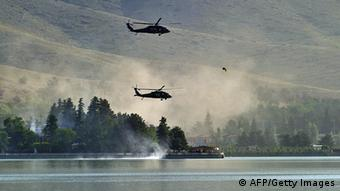 NATO UH-60 Black Hawk helicopters fly near the Spozhmai Hotel in Qargha lake in the outskirts of Kabul Photo: AFP PHOTO / Massoud HOSSAINI (Photo credit should read MASSOUD HOSSAINI/AFP/GettyImages)