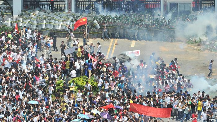 Chinese demonstrators disperse after tear gas was fired during a protest over the Diaoyu islands issue, known as the Senkaku islands in Japan, in Shenzhen, south China's Guangdong province on September 16, 2012. Thousands of anti-Japanese demonstrators mounted protests in cities across China on September 16 over disputed islands in the East China Sea, a day after an attempt to storm Tokyo's embassy in the capital. CHINA OUT AFP PHOTO (Photo credit should read AFP/AFP/GettyImages)
