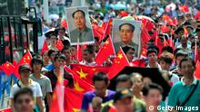Chinese demonstrators carry national flags and portraits of Mao Zedong during a protest over the Diaoyu islands issue, known as the Senkaku islands in Japan, in Wuhan on September 16, 2012. Thousands of anti-Japanese demonstrators mounted protests in cities across China on September 16 over disputed islands in the East China Sea, a day after an attempt to storm Tokyo's embassy in the capital. CHINA OUT AFP PHOTO (Photo credit should read AFP/AFP/GettyImages)